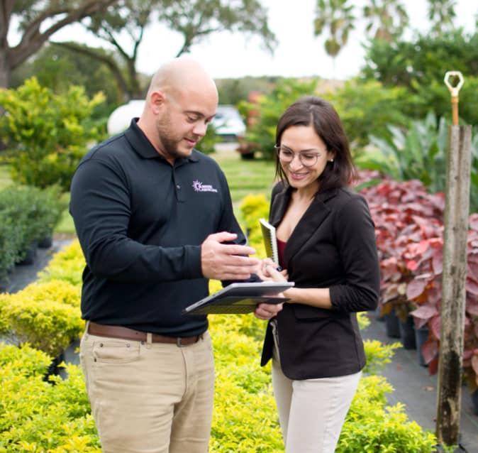 Sunrise Landscape account manager reviewing landscape plans with client with plants in background