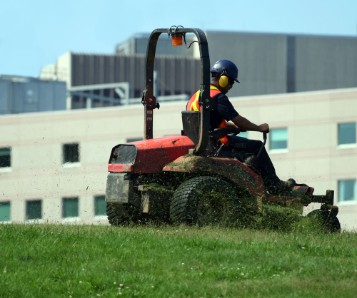 Worker mowing turf with riding mower