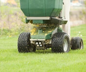 Machine placing fertilizer on lawn